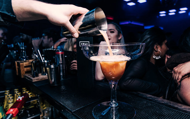 A man pouring cocktails in a nightclub
