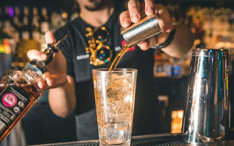 A man pouring whisky into a large glass