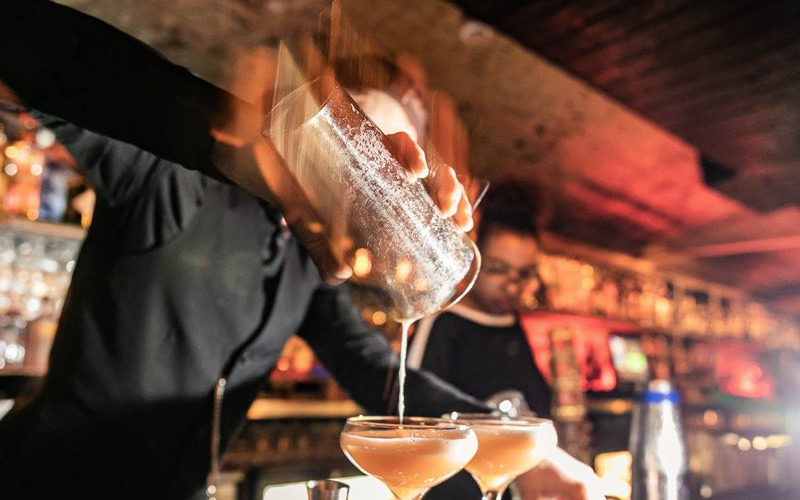 A man pouring a cocktail mixture into several glasses