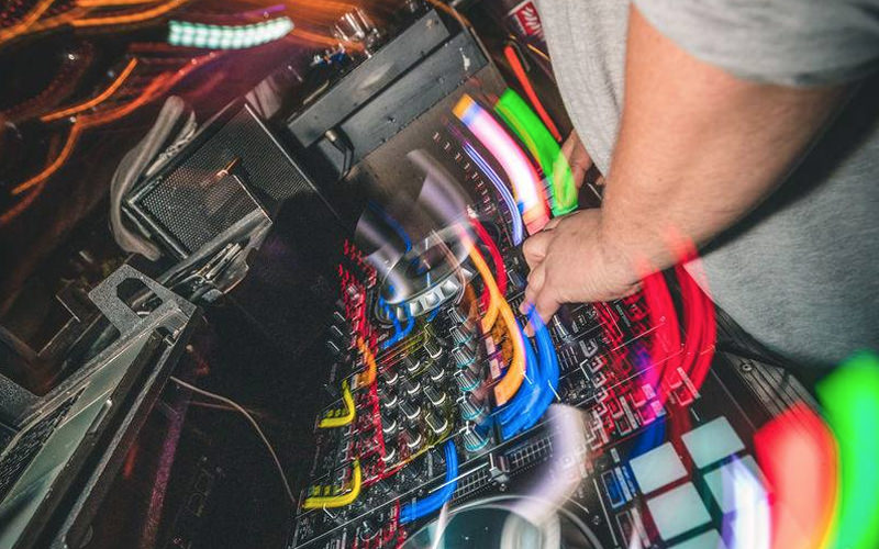 A DJ pressing buttons while brightly coloured lights flash around him
