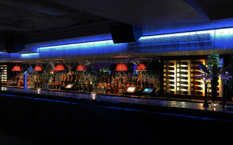 A long nightclub bar with several bottles of alcohol behind it