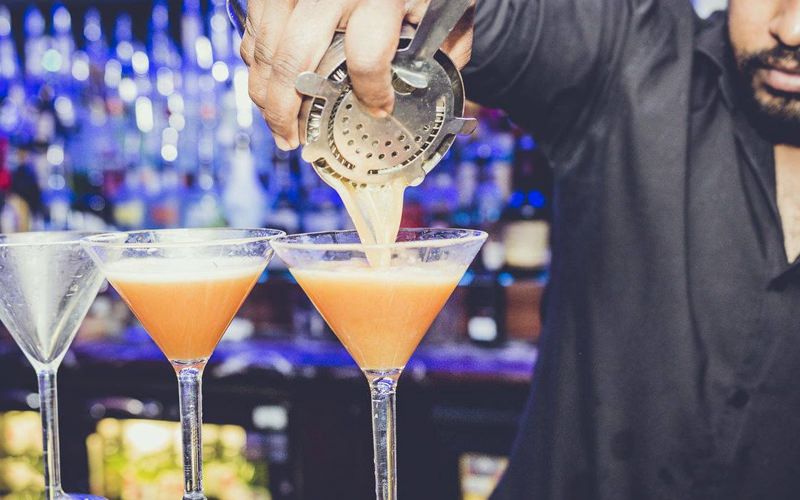 A man pouring an alcoholic mixture into a cocktail glass