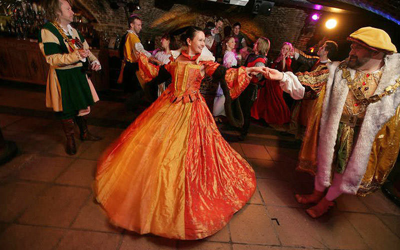 A woman in an orange dress, dancing with a man dressed up