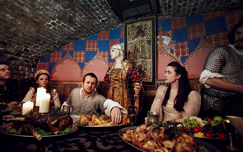 A group of people dressed up in Medieval clothing with food on a table