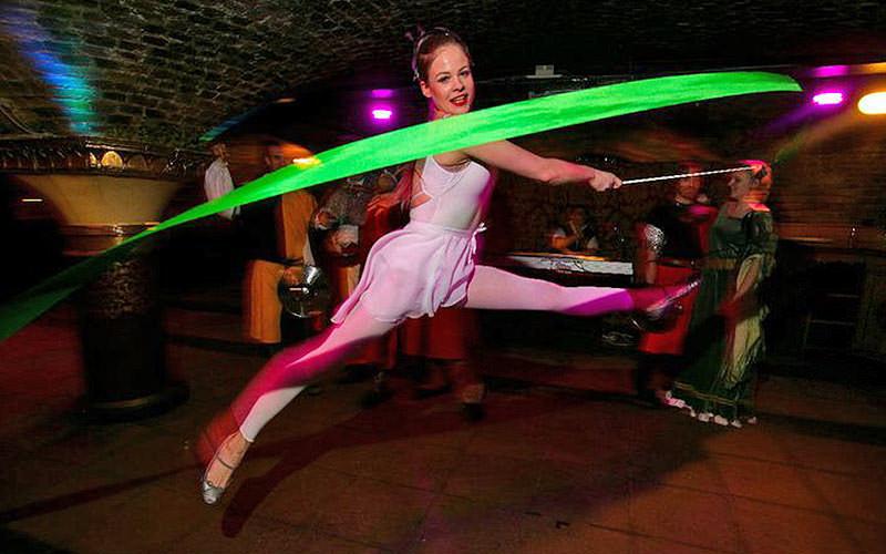 A woman dancing, waving a green ribbon in the air