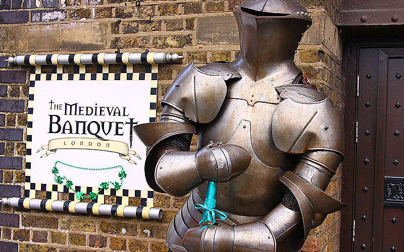 A knight of armour in front of a Medieval banquet sign