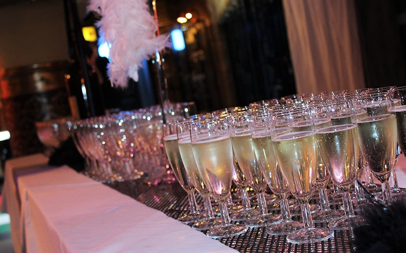 Some glasses of bubbly lined up on a bar