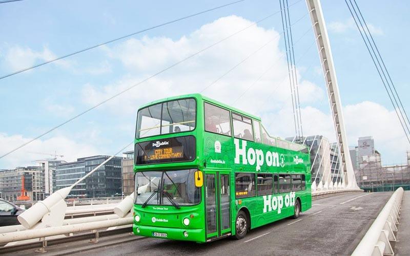 A green sightseeing bus driving across a bridge in Dublin