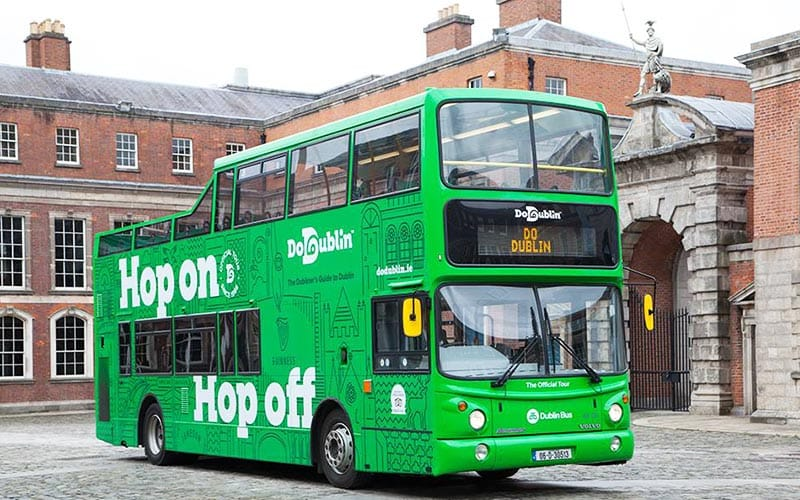 A green sightseeing bus parked outside an attraction in Dublin
