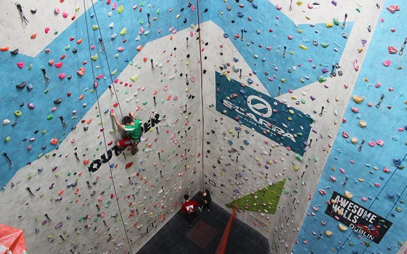 A large climbing wall with a climber climbing it