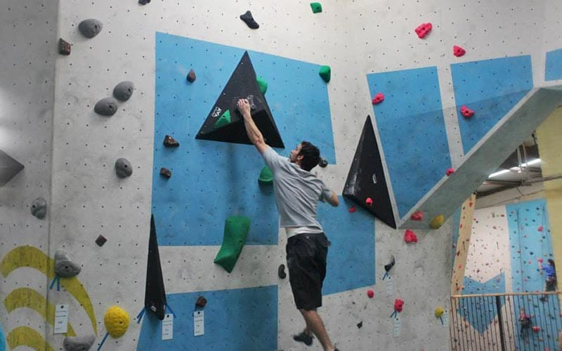 A small climbing wall with a man climbing up it