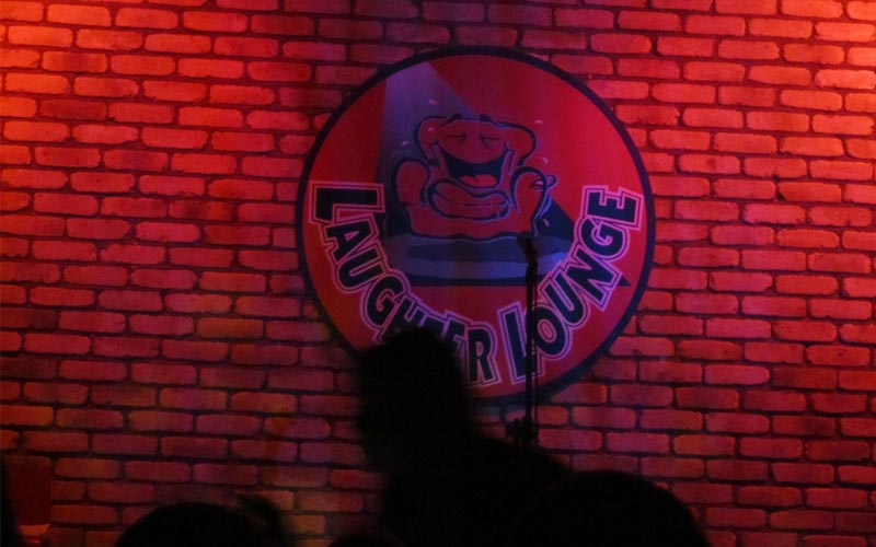 The Laughter Lounge's logo on a brick wall