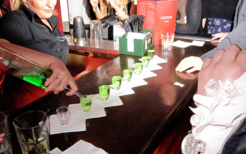 A barmaid pouring lots of green shots on a bar