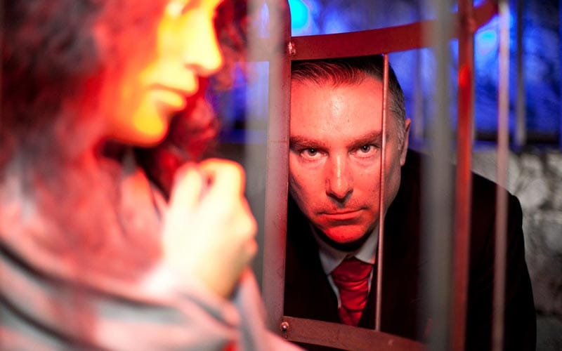 A scary looking man, staring through the bars at the camera, with a woman in the foreground