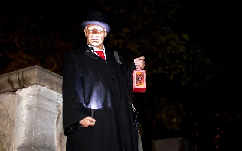 A scary looking man holding a torch up to his face