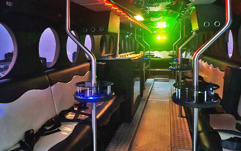 The interiors of a party bus with bar stools and a seating area