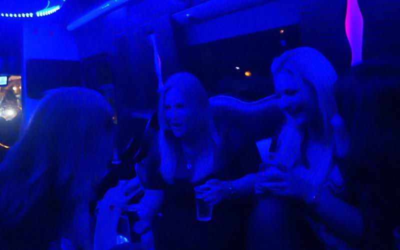 Some girls illuminated in a blue light, on board a party bus