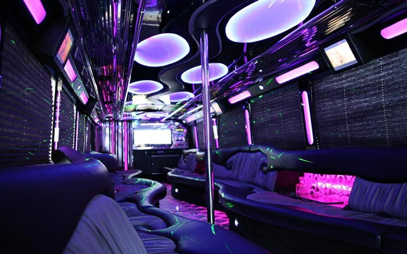 The interiors of a party bus which is neon lit