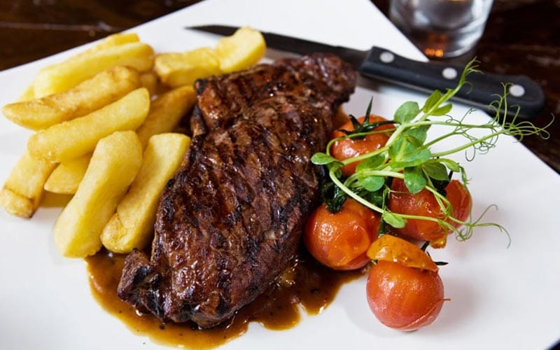 A steak and chips meal on a white plate