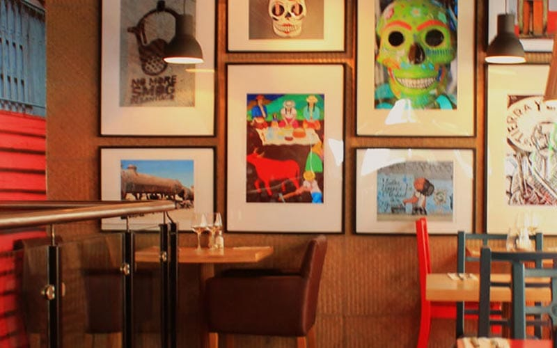 Some framed artwork behind the tables in Dublin's Cactus Jack's restaurant