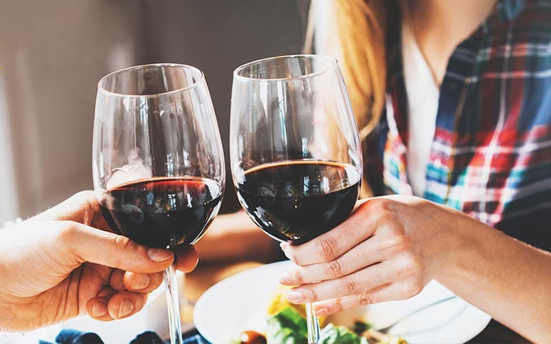 Two people chinking glasses of red wine together