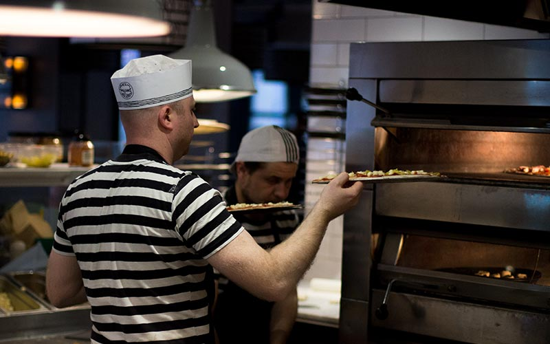 A chef placing two pizzas in an oven