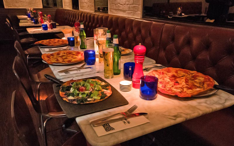 Pizzas served on a table set up for dinner