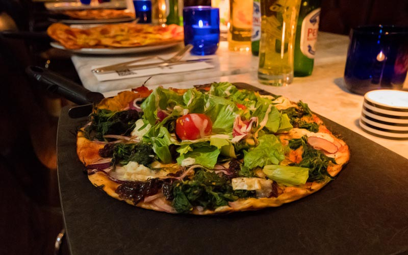 A pizza served up on a black slate