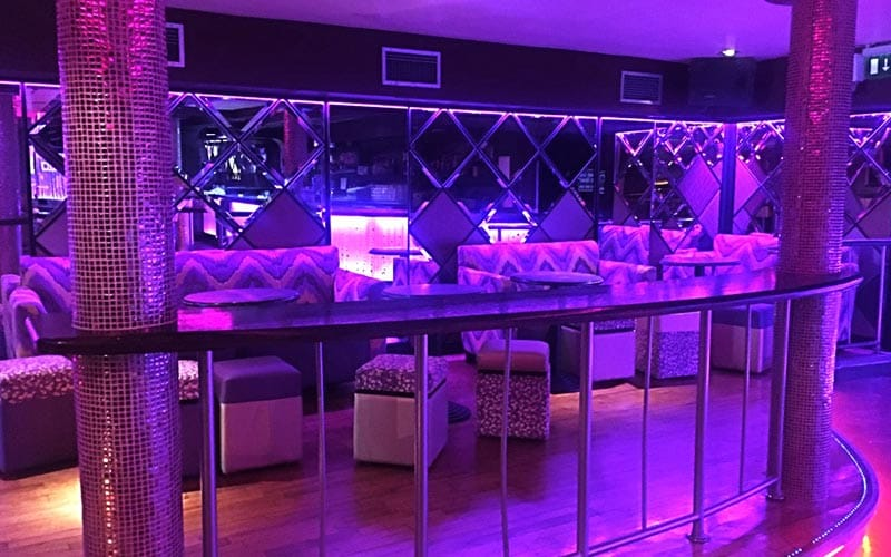 A seating area illuminated in purple, with seats dotted around the room