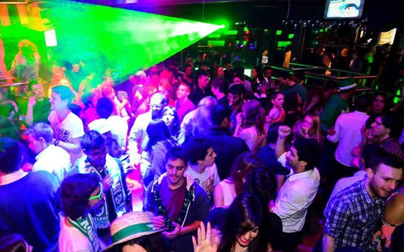 A green spotlight in Dublin's Club M, with people socialising and dancing under it
