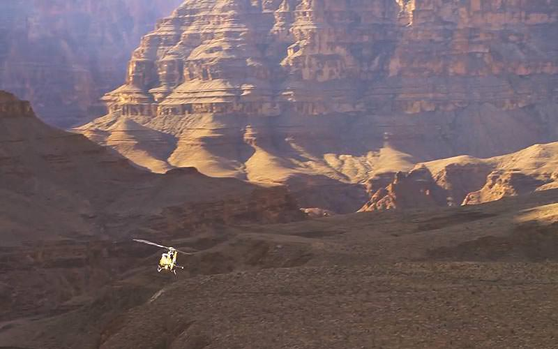 A helicopter flying against a background of the Grand Canyon