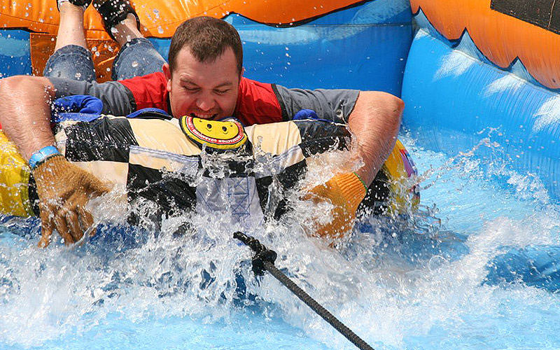 Man face down in inflatable ring being pulled through the water.