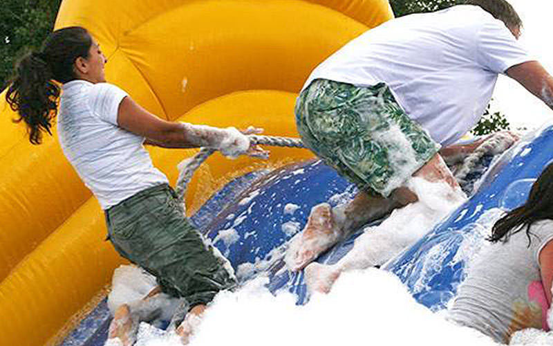 Man and women climbing inflatable slide using a rope with the slide full of bubbles.