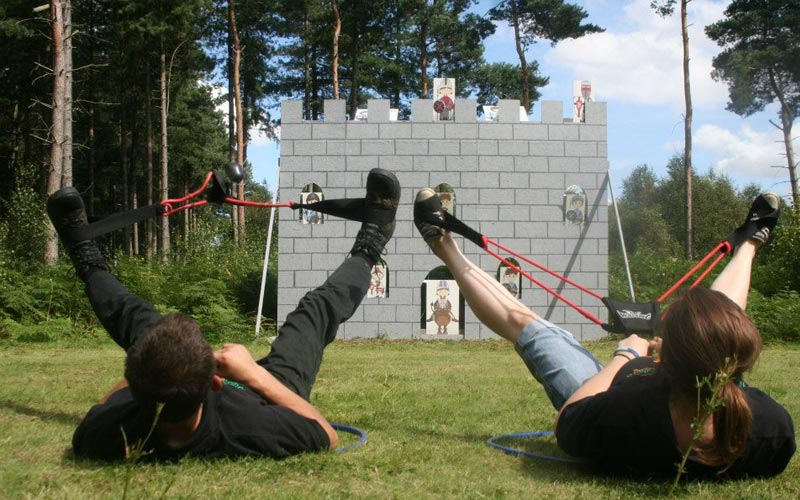 Two girls firing slingshots using their legs