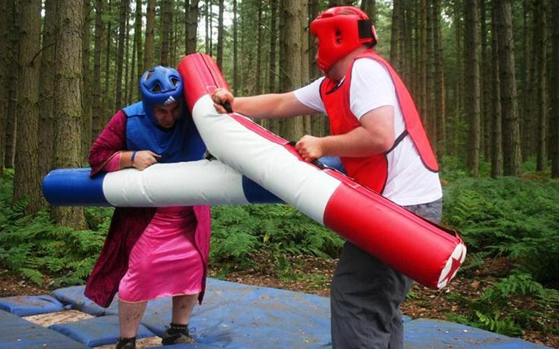 Two people fighting with inflated poles in Sherwood Forest