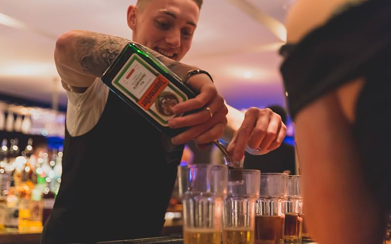 A bar tender pouring a jagerbomb