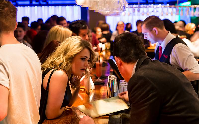 A girl ordering a drink in a busy club