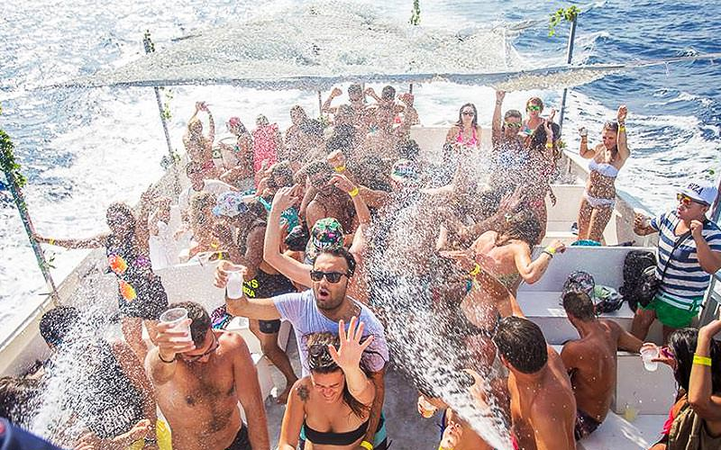 Group of people on the top deck of a boat and getting sprayed on
