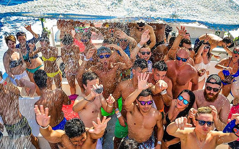 Group of people dancing on the top deck of a boat and getting sprayed on