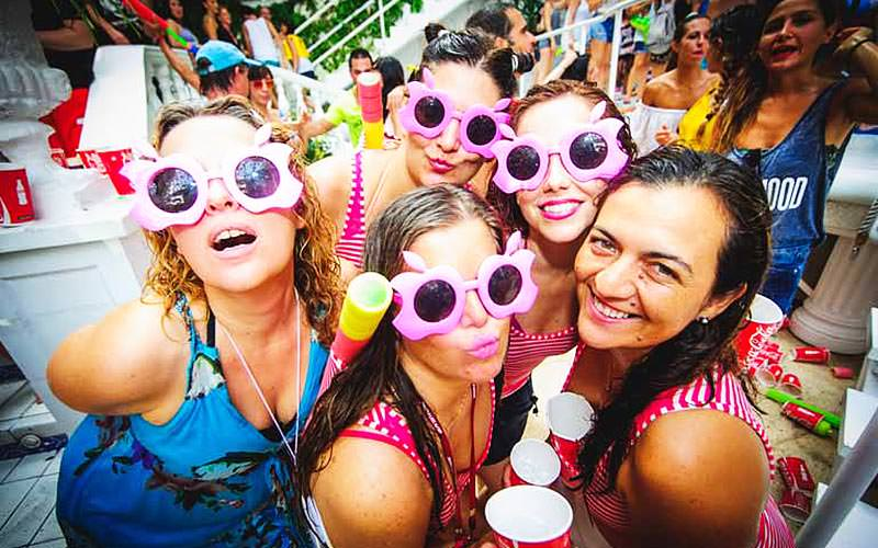 Five girls posing for a picture in pink shades with others in the background