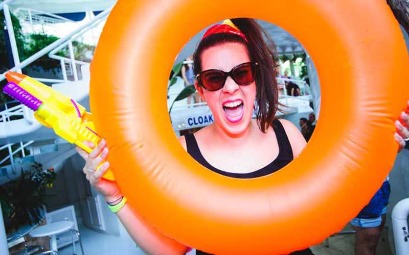 A woman posing with her face between an orange inflatable ring and holding a water gun