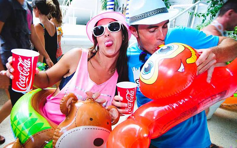 A man and woman posing with inflatables