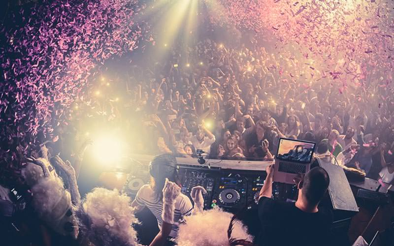 People dancing in a club with pink confetti falling on them, with a DJ booth in the foreground