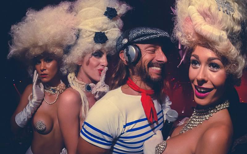 Three women in French-style wigs posing with a man in headphones