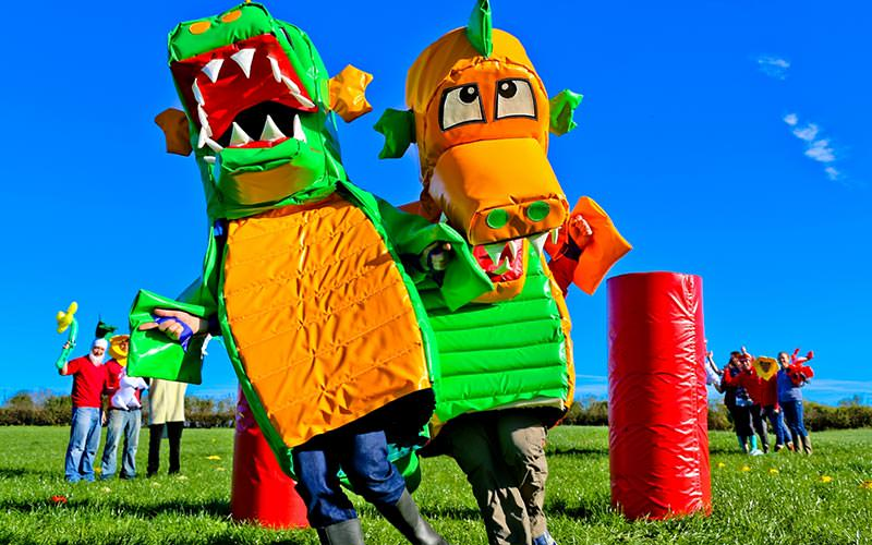 Two men dressed as dragons in a field, with people in costumes and cheering on in the background
