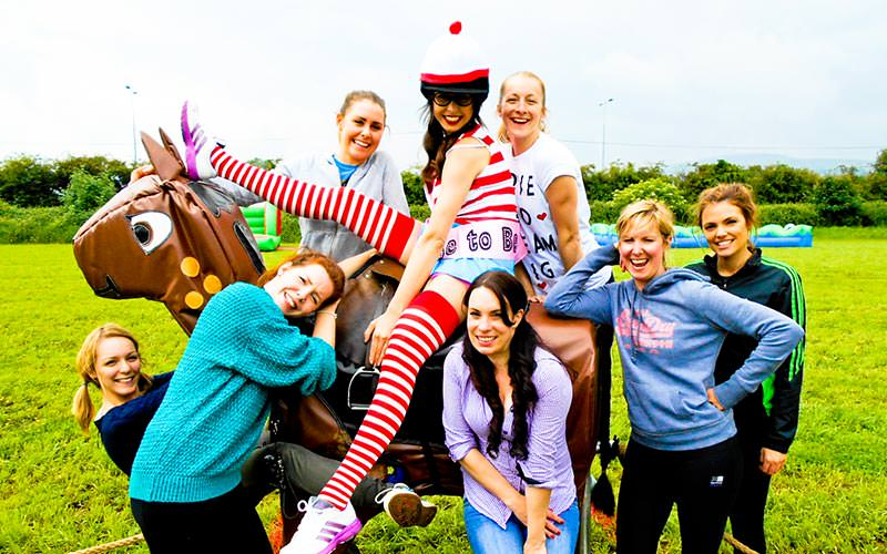 A woman sat on top of a fake horse, posing alongside a group of women