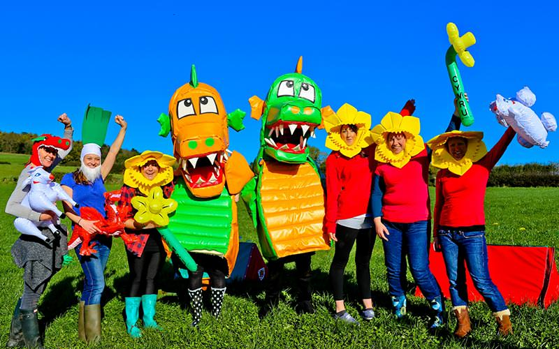 Two people dressed as dragons, along with others dressed as daffodils