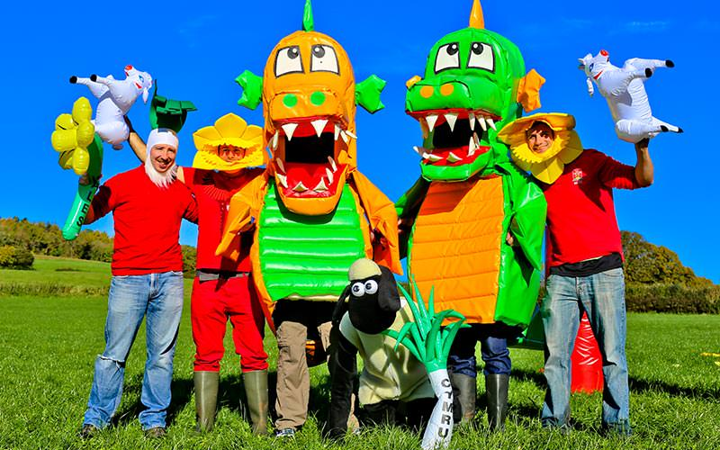 Two people dressed as dragons and three as daffodils, holding inflatable sheep and daffodils