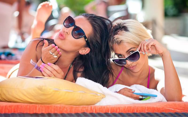 Two girls lying on a sun lounger, on their phones