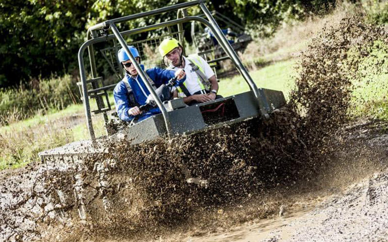 Two men driving buggy through mud